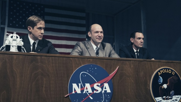 Gosling with Corey Stoll as Buzz Aldrin and Lukas Haas as Mike Collins at the moon launch press conference in First Man